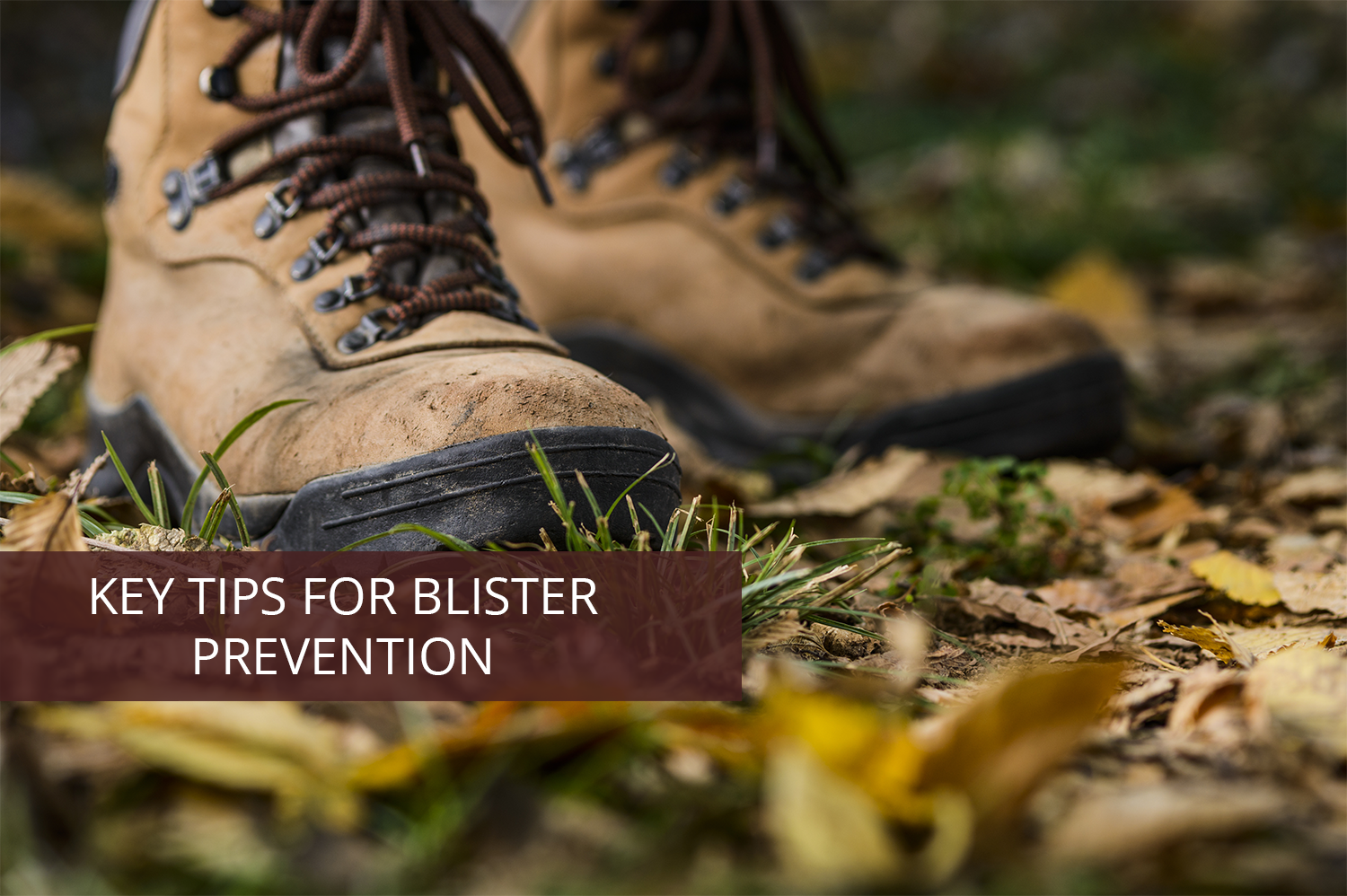 "Hiking boots with yellow leaves underneath them, with banner saying ""Blister Prevention During Your Hunt."""