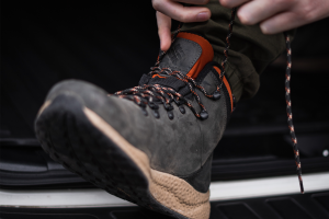 Man tying up his hiking boots tight for blister prevention.