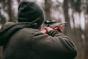 Man with a green beanie holding a rifle during a fall hunt.