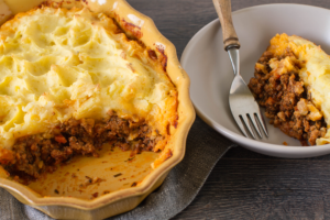 shepherd's pie in a yellow baking dish with a scoop of it on a plate with a fork.