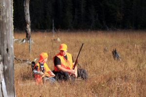 Father and son dressed in orange vest and hats sit on a log during their family hunting trip.